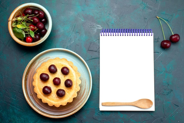 Top view of cupcake with cherries next to cherries and notebook
