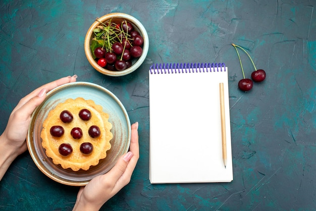 Top view of cupcake with cherries which someone holds next to notebook