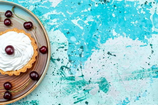 Top view of cupcake with sour cherries and cream on light blue and white,
