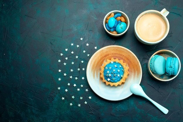 Top view of cupcake with stars and blue chocolate next to cup of coffee and macaroons