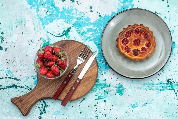 Vista dall'alto di cupcake con frutti di bosco gustosi accanto al cucchiaio forchetta e piatto di fragole su azzurro e bianco,