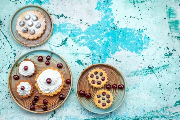 Vista dall'alto di cupcakes con ciliegie e tutti i diversi stili