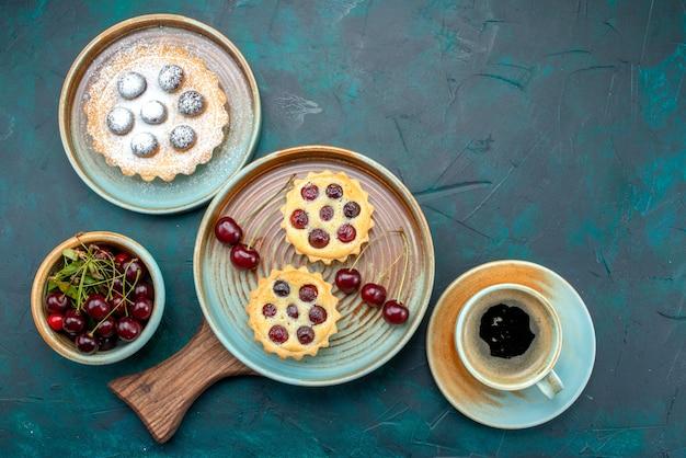 Vista dall'alto di cupcakes con ciliegie accanto all'americano sul blu, Foto Gratuite