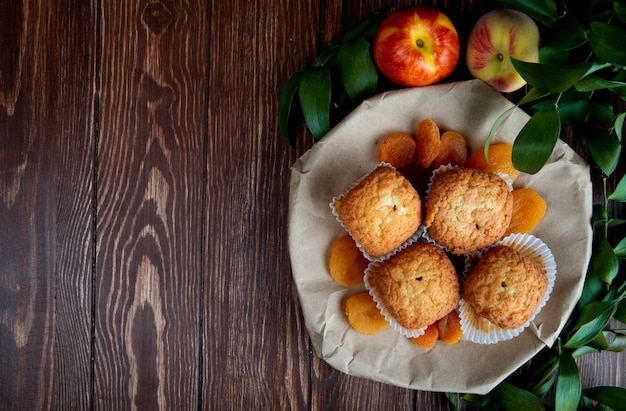 Top view of cupcakes with dried plums in plate and peaches on wooden surface decorated with leaves with copy space