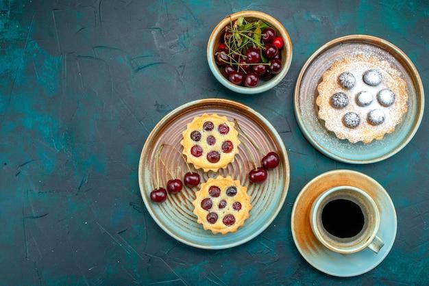 Vista dall'alto di cupcakes con zucchero in polvere e ciliegie fresche vicino americano caldo e piatto di ciliegie