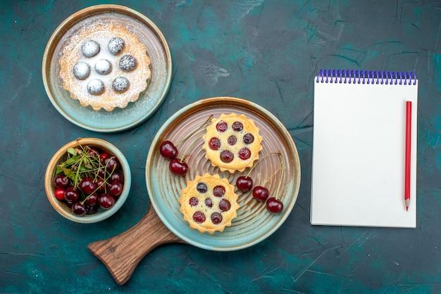 Vista dall'alto di cupcakes con ciliegie gustose vicino al taccuino e un altro cupcake