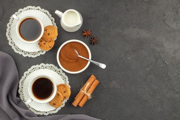 Top view cups of coffee cinnamons cookies milk cup cocoa powder in bowl on dark surface