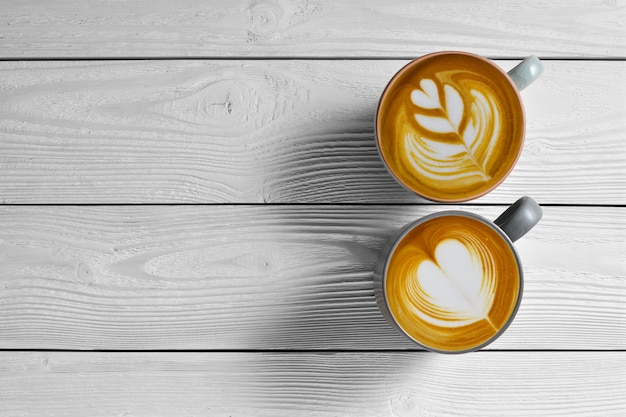 Top view of cups of coffee latte on white wooden background