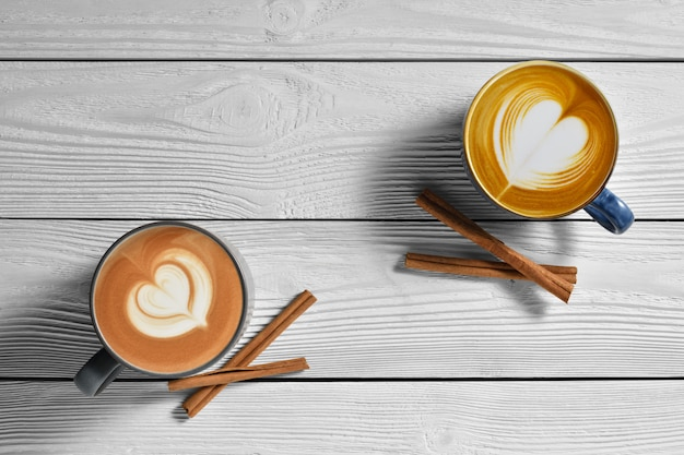 Top view of cups of coffee latte with cinnamons on white wooden background