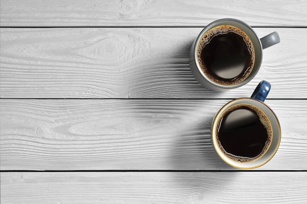 Top view of cups of coffee on white wooden background