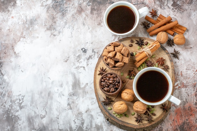 Top view cups of coffee with cinnamon and walnuts on light background sugar tea color cookie sweet cocoa