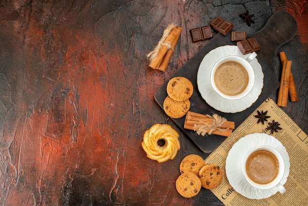 Top view of cups of coffee on wooden cutting board and an old newspaper cookies cinnamon limes chocolate bars on dark background