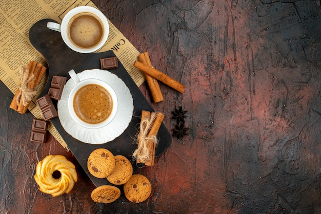 Top view of cups of coffee on wooden cutting board and an old newspaper cookies cinnamon limes chocolate bars on the right side on dark background