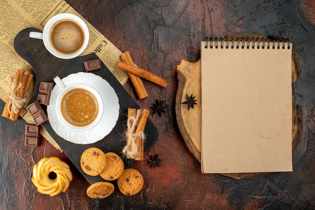 Top view of cups of coffee on wooden cutting board and an old newspaper cookies cinnamon limes chocolate bars next to spiral notebook on dark background