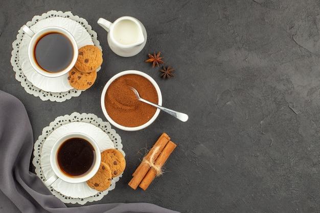 Вид сверху чашки кофе с корицей, печенье, чашка с молоком, какао-порошок в миске на темной поверхности