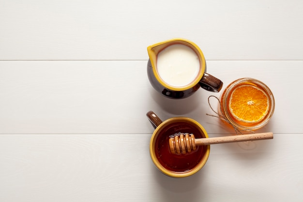 Top view cups with milk and tasty honey