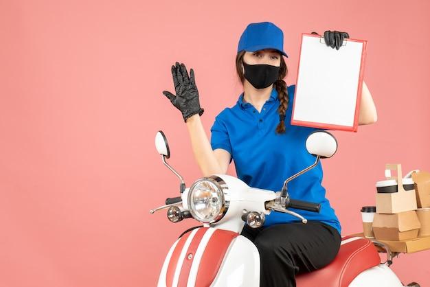 Vista dall'alto della curiosa ragazza del corriere che indossa maschera medica e guanti seduti su uno scooter con in mano un foglio di carta vuoto che consegna ordini su sfondo color pesca pastello
