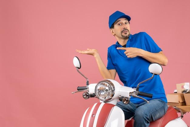 Vista dall'alto di un curioso corriere che indossa un cappello seduto su uno scooter che consegna ordini indicando qualcosa su sfondo color pesca pastello