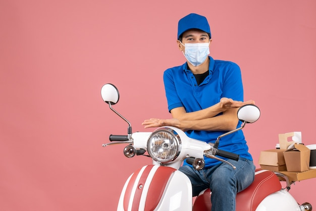 Top view of curious courier man in medical mask wearing hat sitting on scooter on pastel peach background
