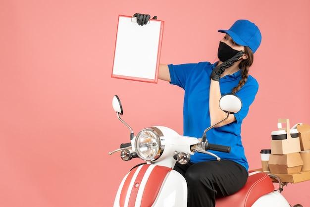 Vista dall'alto di una curiosa donna corriere che indossa maschera medica e guanti seduta su uno scooter con in mano fogli di carta vuoti che consegnano ordini su sfondo color pesca pastello