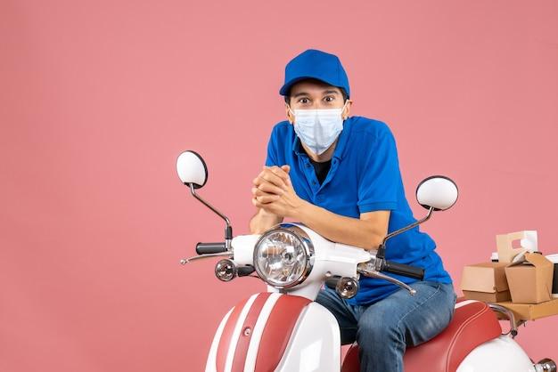 Vista dall'alto del ragazzo delle consegne curioso in maschera medica che indossa un cappello seduto su uno scooter su sfondo color pesca pastello