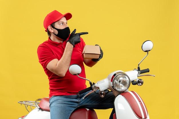 Vista dall'alto del ragazzo delle consegne curioso che indossa guanti di camicetta e cappello rossi in mascherina medica che si siede sullo scooter che mostra l'ordine