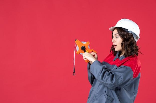 Vista dall'alto di una curiosa architetto donna in uniforme con elmetto che tiene il nastro di misurazione su sfondo rosso isolato