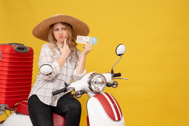 Top view of curious young woman wearing hat and sitting on motorcycle and holding ticket on yellow