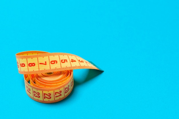 Top view of curled measuring tape as a sewing accessory on blue background. tailor concept with copy space