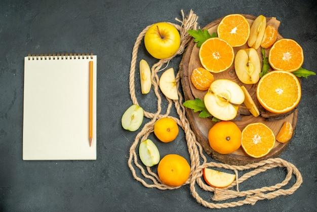木の板にリンゴとオレンジをカットした上面図は、暗い背景にノートブックと鉛筆をカクテルします