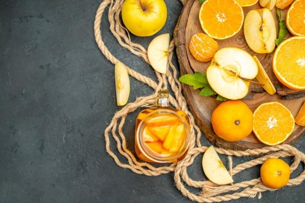 暗い背景の上の木の板のカクテルにリンゴとオレンジをカットした上面図