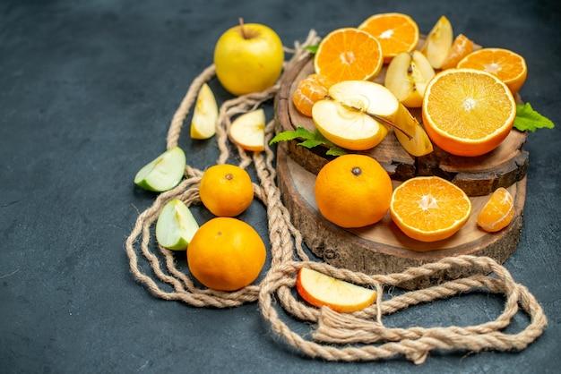 Vista dall'alto tagliare mele e arance su tavola di legno cocktail su sfondo scuro