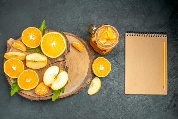 Vista dall'alto tagliare mele e arance su tavola di legno cocktail un quaderno su sfondo scuro