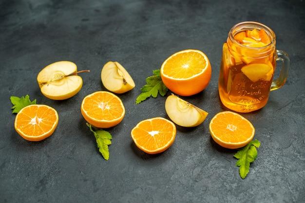Vista dall'alto tagliare arance e mele tagliate cocktail su sfondo scuro