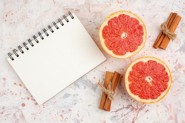Вид сверху нарезанные грейпфруты палочки корицы блокнот на обнаженной поверхности