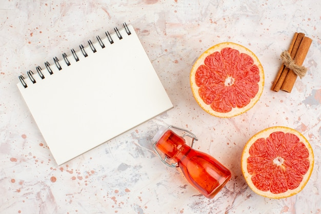 Top view cut grapefruits cinnamon sticks bottle a notepad on nude surface
