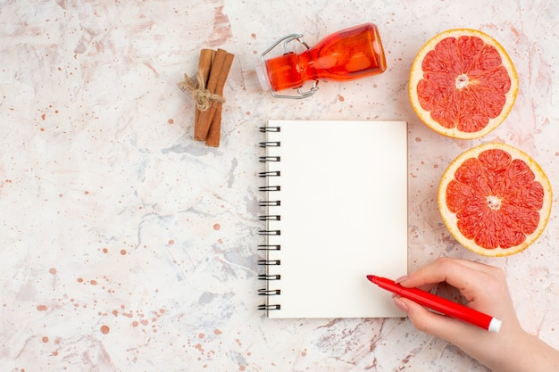 Top view cut grapefruits cinnamon sticks bottle notepad red marker in female hand on nude surface with copy space