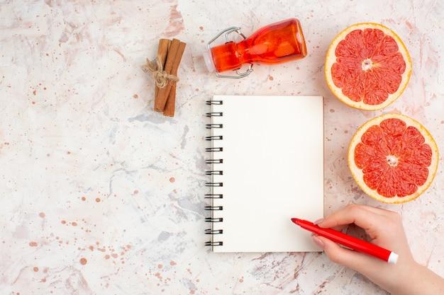 Vista dall'alto pompelmi tagliati bastoncini di cannella bottiglia notepad pennarello rosso in mano femminile su superficie nuda con spazio di copia