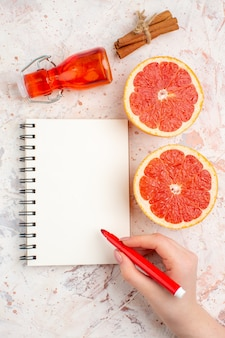 Top view cut grapefruits cinnamon sticks bottle notepad red marker in female hand on nude surface