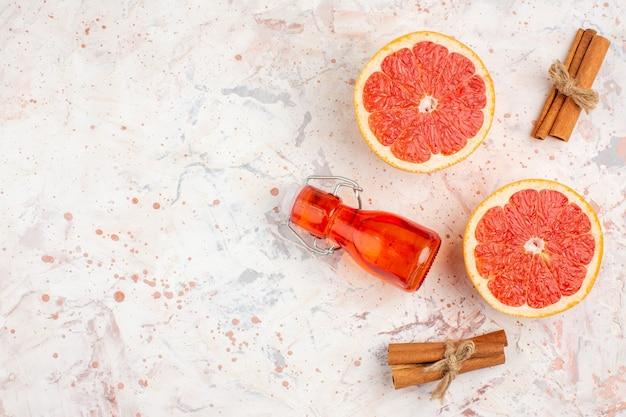 Вид сверху нарезанные грейпфруты бутылка палочек корицы на обнаженной поверхности с копией пространства