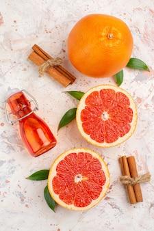 Вид сверху нарезанные грейпфруты бутылка свежего грейпфрута с корицей на обнаженной поверхности