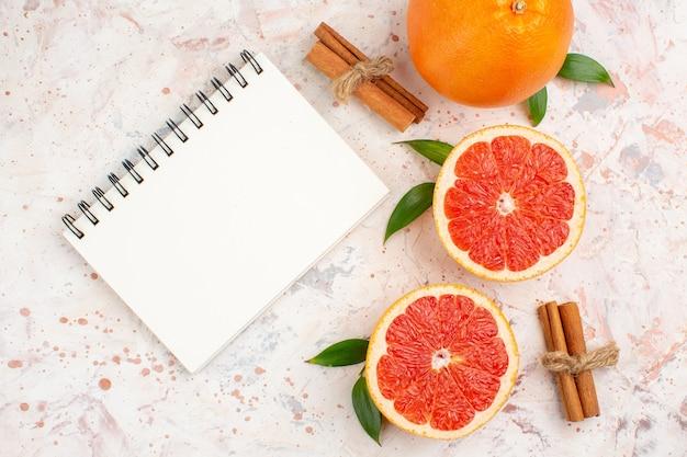 Вид сверху нарезанный грейпфрут, свежий грейпфрут, корица, блокнот на обнаженной поверхности