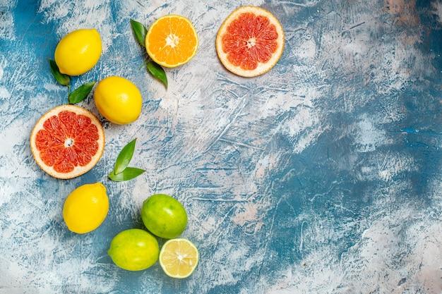 Вид сверху нарезанные грейпфруты, лимоны на синей белой поверхности, свободное место