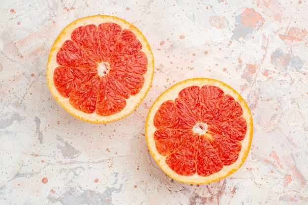 Top view cut grapefruits on nude surface