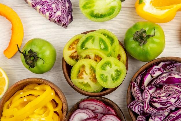 상위 뷰 흰색 바닥에 나무 그릇에 녹색 토마토 노란 피망 붉은 양배추 붉은 양파를 잘라