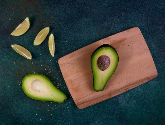 La vista superiore ha tagliato in mezzo avocado su una lavagna con il limone su un fondo verde scuro