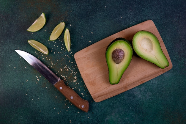 Top view cut in half avocado on a blackboard with lemon and knife on a dark green background