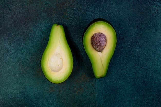Vista dall'alto tagliato a metà avocado su uno sfondo verde scuro