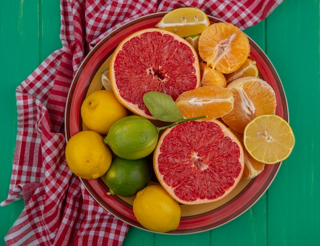 Vista dall'alto tagliato a metà pompelmo con arance sbucciate e limone con lime su un piatto su un asciugamano a scacchi rosso su sfondo verde