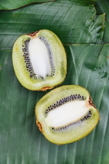 Top view of cut half thai kiwi on banana leaves. example fruity taste of coffee.